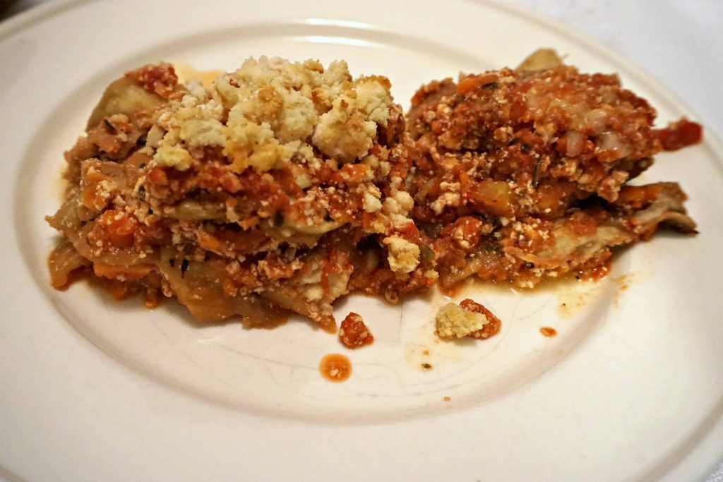Portions of Vegan Eggplant Lasagna and Vegetarian Eggplant Lasagna side by side on a white plate